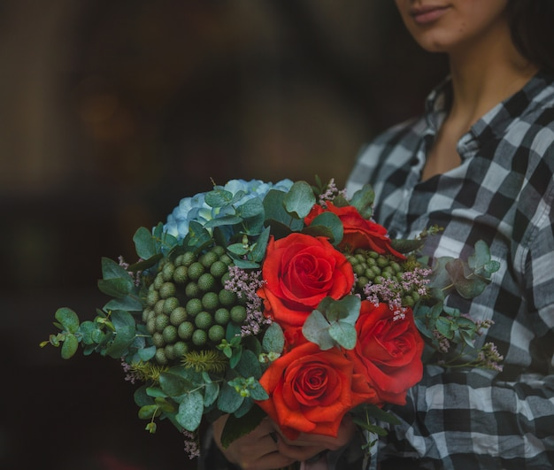 A woman holding a bouquet of red velvet roses and green blossoms in the hand on street