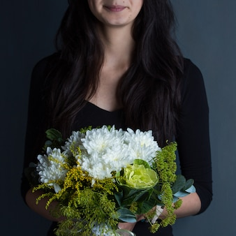 A woman holding a bouquet of snow white flowers in the hand in shooting space