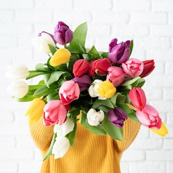 Woman holding bouquet of tulips in front of her face