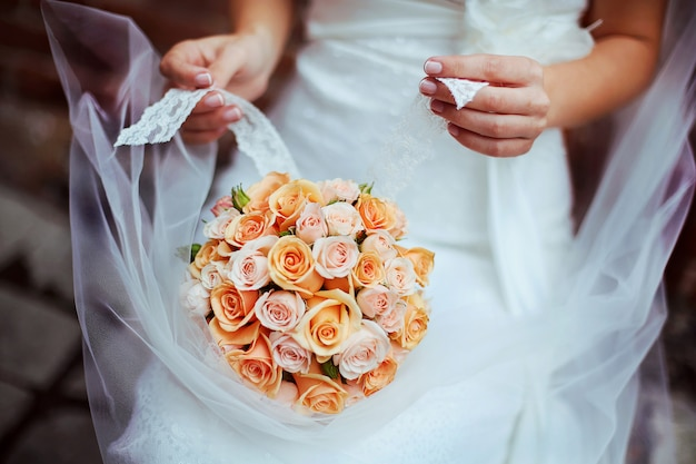 Woman holding  bouquet with her hands on wedding day.