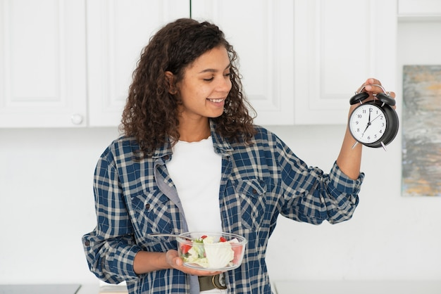 Woman holding a bowl a salad and a clock