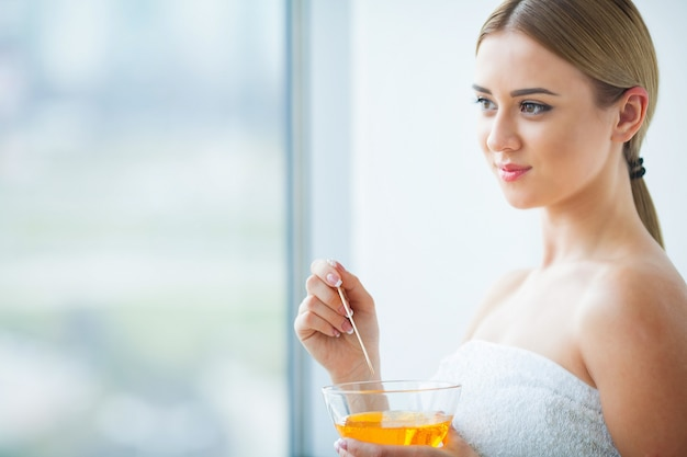 Woman holding a bowl of wax for depilation