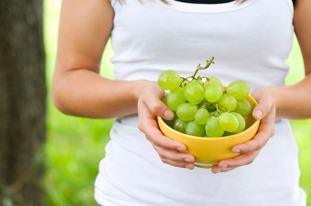 Женщина, держащая миску с виноградом