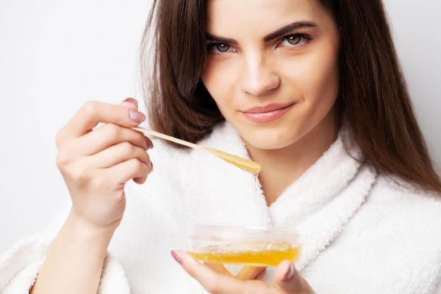 Женщина держит миску с воском для удаления волос
