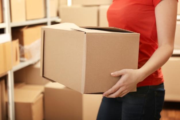 倉庫で箱を保持している女性