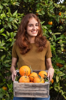 Woman holding a box full of oranges in her hands