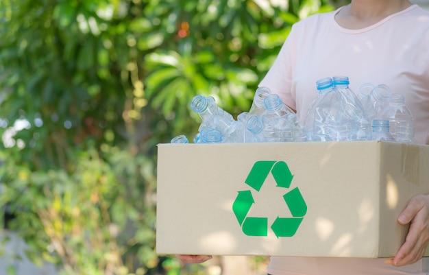 ペットボトルのゴミやリサイクルのボックスを保持している女性。世界環境デーまたは再利用の概念。