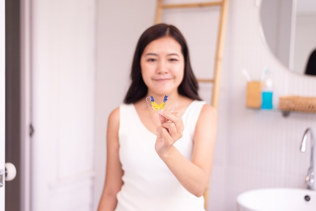 Woman holding braces teeth or silicone trainer,orthodontic,dental health concept,decayed tooth