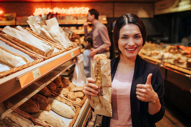 Woman holding bread at grocery store and with thumb up