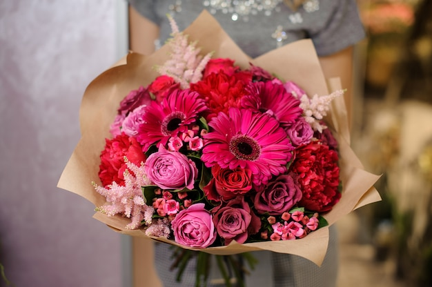 Woman holding a bright pink flower bouquet