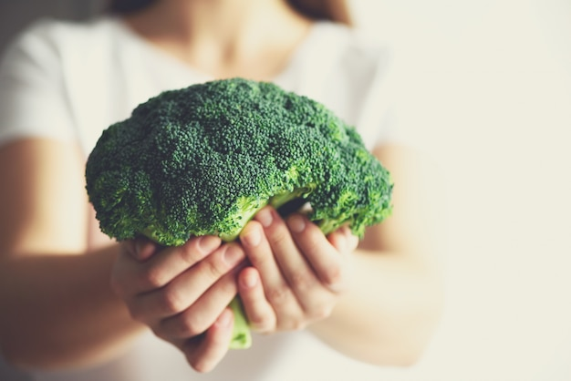 Woman holding broccoli in hands. copy space. healthy clean detox eating concept. vegetarian, vegan, raw concept