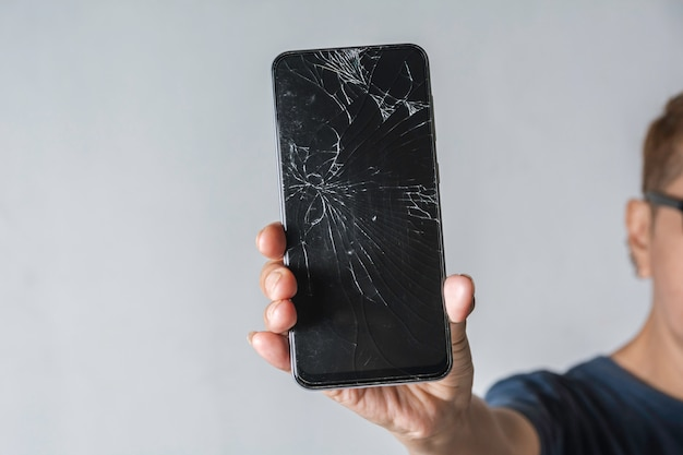 Woman holding a broken touch screen of smart phone on grey background.