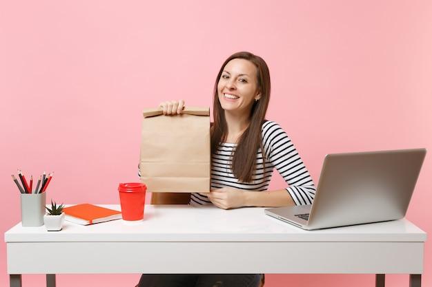 Женщина, держащая коричневый ясный пустой пустой бумажный мешок ремесла, работа в офисе с компьтер-книжкой пк изолированной на розовой предпосылке. доставка продуктов курьерской службой из магазина или ресторана в офис. скопируйте пространство.