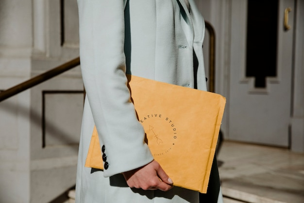 Woman holding a brown envelope mockup in front of a building