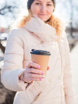 屋外で茶色の紙のコーヒーカップを保持している女性。
