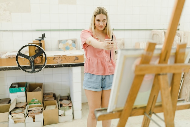 Woman holding brush in front of easel winking at workshop
