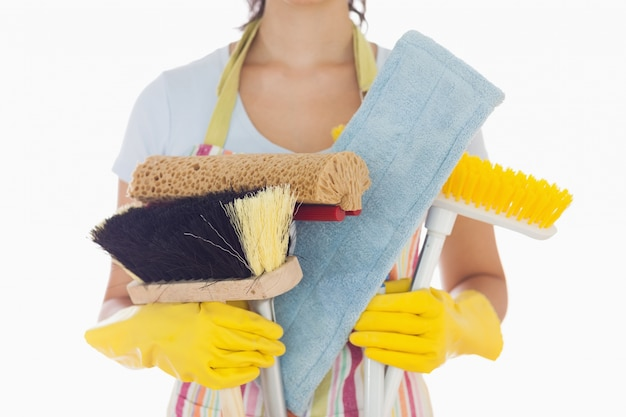 Woman holding brushes and mops