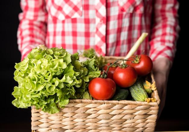 Woman holding a bucket of veggies