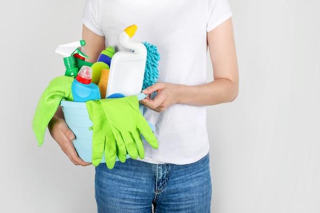 クリーニング製品でバケツを保持している女性