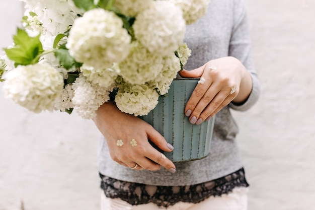 Woman holding a bucket with hydrangea flowers