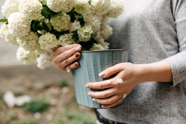 Woman holding a bucket with seasonal white flowers