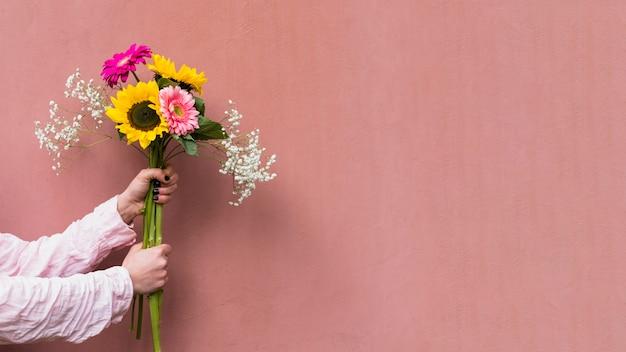 新鮮な花の束を保持している女性