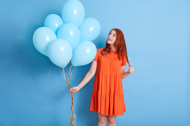 Женщина, держащая букет гелиевых шаров, смотрит на ее подарок с удивленным и возбужденным выражением лица