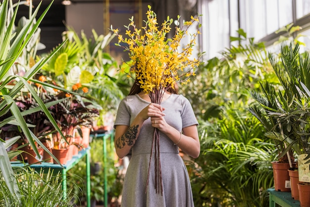 Woman holding bunch of twigs near face between green plants