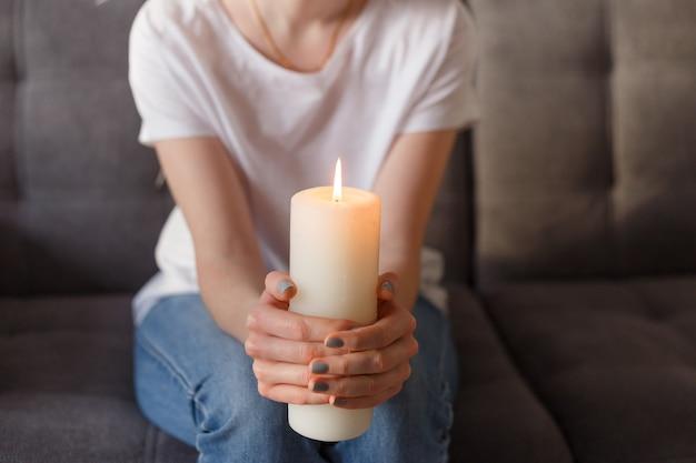Женщина держит горящую свечу в руках.