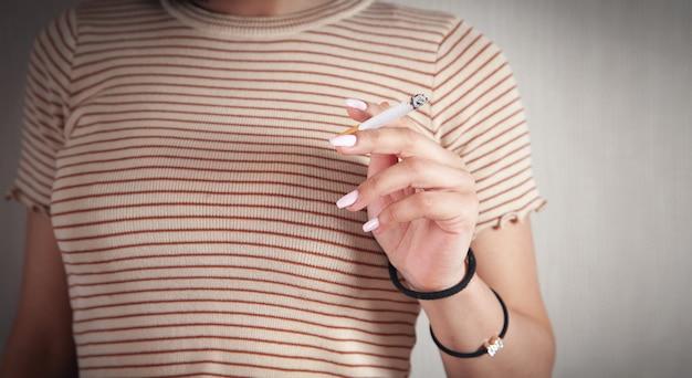 Женщина, держащая горящую сигарету. курение