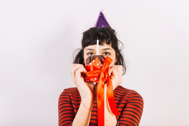 Woman holding cake in front of her face with ribbon and candle over white background