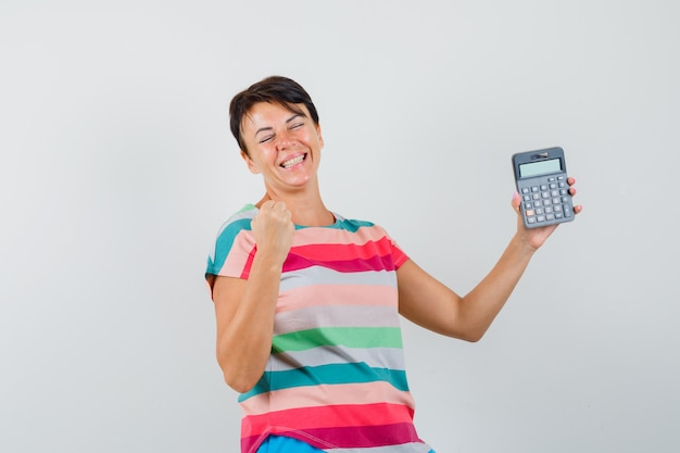 Woman holding calculator in striped t-shirt and looking blissful
