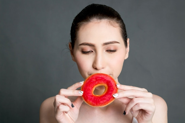Woman holding calorie bomb donut on gray background