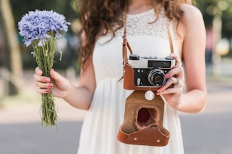 Woman holding camera and flowers