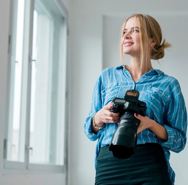 Woman holding a camera and looking through windows