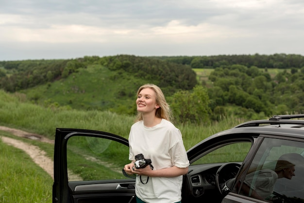 Woman holding camera in nature with car