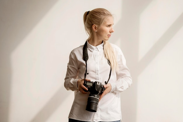 Woman holding a camera photo looking away