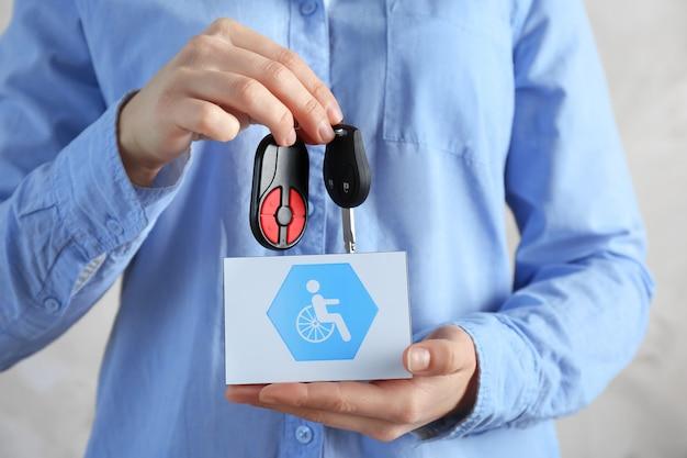 車のキーとハンディキャップサイン、クローズアップとカードを保持している女性