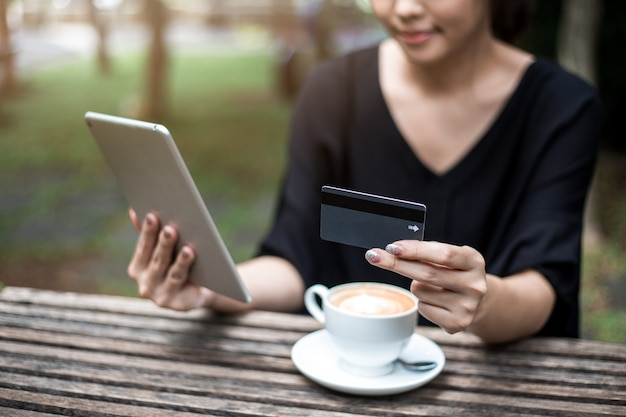 Woman holding card and tablet for shopping online.