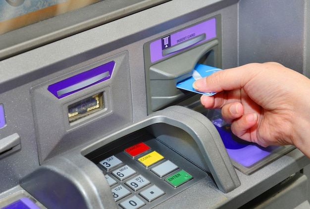 Woman holding card ,using atm