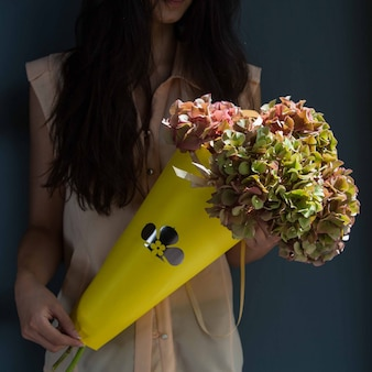 A woman holding a cardboard bouquet of yellow leaf flowers in the hand on a room wall