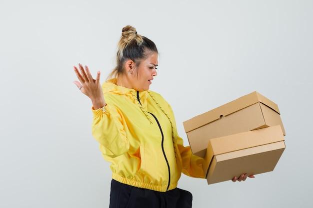 Женщина держит картонные коробки в спортивном костюме и выглядит запутанной. передний план.