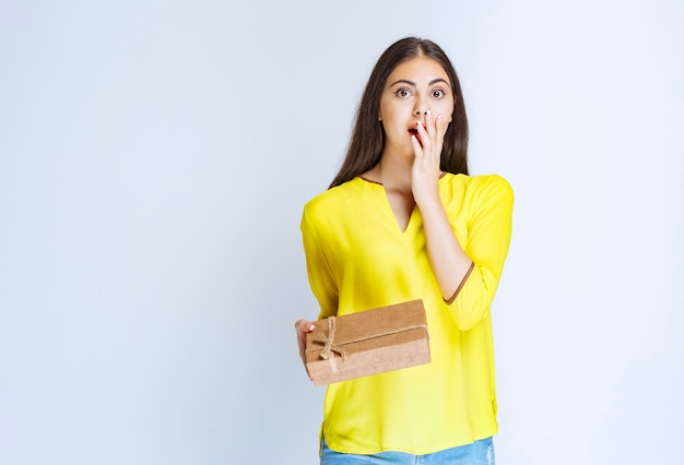Woman holding a cardboard gift box and looks confised or thoughtful.
