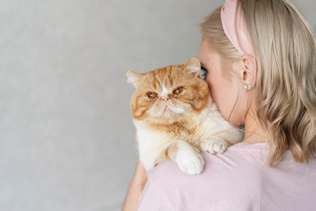 Женщина, держащая кошку крупным планом