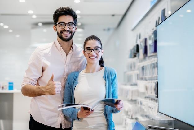 Женщина, держащая каталог и человек, дает большие пальцы, пока они стоят в магазине технологий. современные технологии.