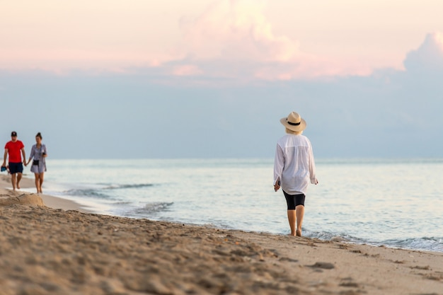Woman holding cell phone and wearing straw hat walking on a beach at sunset