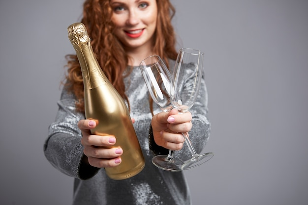 Woman holding champagne flute and bottle
