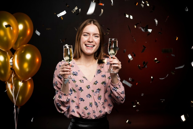 Woman holding champagne glasses surrounded by confetti and balloons