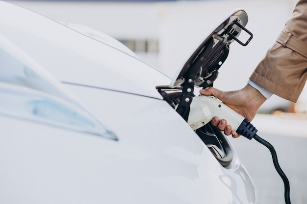充電器を持って電気自動車を充電している女性のクローズアップ
