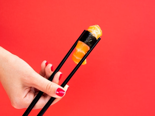 Woman holding in chop sticks a salmon sushi on a red background